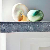 Stuckprofil, Farbgestaltung und Dekogegenstände ergänzen sich bei dieser schlichten Kamineinfassung perfekt.