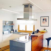 Der Mix von warmen Holz-, kühlen Metallflächen und dem Weiß der Stuckprofile verleiht dieser Küche ihre Atmosphäre.