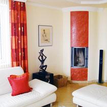 Knallige Farbakzente und elegant geschwungene Stuckprofile erwecken dieses Wohnzimmer zum Leben.