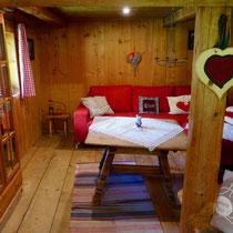 Das Wohnzimmer mit großem Sofa und Ofen.
