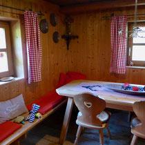 Im Wohnzimmer hat es einen großen Esstisch mit Eckbank.