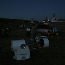 Plantada de telescopios con las cabañas y tipis al fondo.