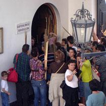 Tinos: Große Kerzen am äußeren Tor abliefern