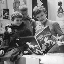 """Cécile Aubry montre son livre """"Les Vacances de Lumineux, Petit Cheval de Cirque"""" à deux enfants. © ebay"""