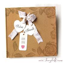 Hochzeitsgästebuch im Vintage-Stil mit beigefarbenem, floral bedruckten Einband mit Schleife aus weißer Spitze und personalisierten Labels u.a. in Herzform.