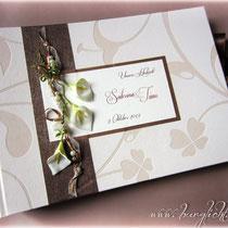 Fotoalbum zur Hochzeit mit weißen Callas - Der Einband ist mit verschiedenen elfenbein- und kupferfarbenen Materialien bezogen. Es hat ein stattliches Querformat von 35cm x 25cm und ist mit einem dunkelbraunen Schleifenverschluss aus Satinband versehen.