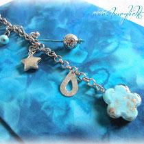 Auf dem Cover ist eine silberfarbene Kette mit Accessoires (Stern, Blume, Perlen,...) in silberfarben, türkis und hellblau befestigt.