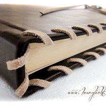 Ledereinband mit dekorativer, umlaufender Flechtung aus naturfarbenem Velourleder-Flachband.