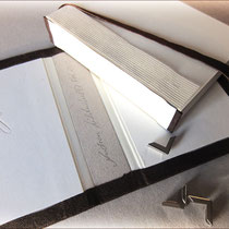 Die individuell angefertigte Einbanddecke und der fertige, 140 Blatt umfassende Buchblock mit geradem Rücken, bereit für die Verbindung. Zum Schutz vor Gebrauchsspuren werden ganz zum Schluss kleine, silberfarbene Metall-Buchecken angebracht.