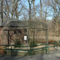 """Voliere für Papageienvögel Tierpark Berlin. Dieser Käfig steht völlig allein, umgeben von total unverbautem Terrain. Man frägt sich deshalb: """"Warum wurde er nicht grosszügiger gebaut ?"""""""