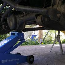 Achse hoch, Räder ab, mit Böcken die Karosserie sichern, Achse langsam und kontrolliert ablassen.