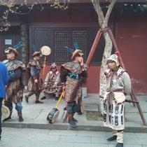 Noch mehr verkleidete Leute vor einem Tempel.