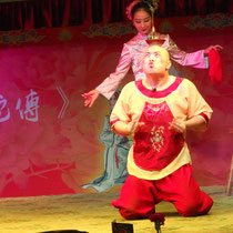 Eine andere Aufführung, eine Art Theaterstück, in dem es darum ging, dass eine Frau ihren Mann tyrannisiert, indem sie ihn zwingt, eine Schüssel mit einer Flamme auf seinem Kopf herumzubalancieren :D