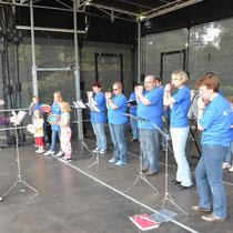 Hier versammeln sich die Musikerinnen und Musiker des Spielmannszug Harmonie Bad Homburg e.V., die gerade nicht einen Stand besetzen müssen, zu einem musikalischen Abschiedsgruß, wiederrum dirigiert von Marco Behrendt