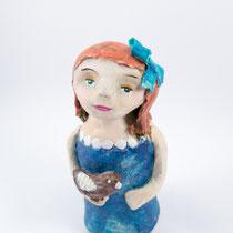 Girl with bird clay doll