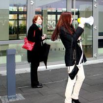 Nadja Naumann, STRABAG Real Estate GmbH, führt die Gruppe mit Megaphon durch das Torhaus.