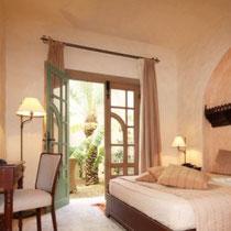 Chambre Habayla  Au rez-de-chaussée, fenêtres sur patio et sur jardin, grand lit, douche, accès jardin.