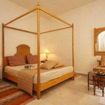 Chambre Abbas: Au rez-de-chaussée, grand lit, baignoire et fenêtre sur patio.