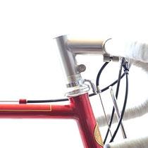 カーボン素材を使わないという目標をもって構成されたこの自転車、ステムはティグ製のオーダーメイド。エクステンションは80mm、スタックハイトは65mmで製作しました。ステンレスボルトを含め104g! アウター受けはイリベ製です。