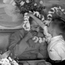 1956 ; Young Larry Karrasch garlanding Meher Baba at Longchamps Restaurant, New York.