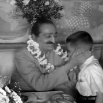 1956 ; Young Larry Karrasch garlanding Meher Baba at Longchamps Restaurant, New York.