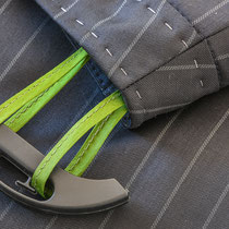 Bündchen eines Nadelstreifenrockes mit grünen Aufhängeschlaufen auf Bügel