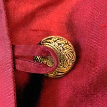 Goldener Knopf mit Schlinge an roter Kostümjacke