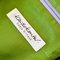 Label des Kleiderkontors auf grünem Futter mit fliederfarbener Taschenpaspelierung