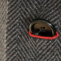 Eingeknoepfter Knopf in Kontraktknopfloch eines Herren-Blazermantel in Fischgrat-Muster