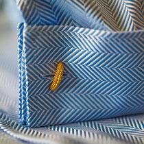 Manschette eines Herrenmaßhemdes in hellblauem Fischgrat-Muster und goldenem Manschettenknopf