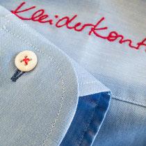 Hellblaues Herrenmaßhemd mit Kontraststickerei des Kleiderkontors in rot, sowohl rot angenähten Knöpfen