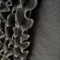 Rüschenkante an schwarzem Damenjäckchen
