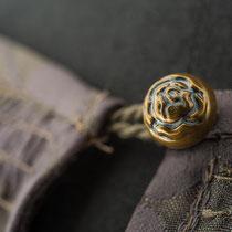 Bronzefarbener Rosenknopf mit Schlinge an Kleiderausschnitt