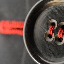 Handgestochenes Knopfloch in Kontrast und Knopf ebenfalls in Rot angenäht