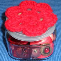 Knopfglas mit roten Knöpfen und roter Häkelblume