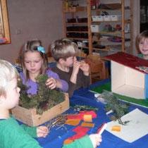 Viola legt die mit Julians Papa Lukas gebaute Krippe mit Moos aus.