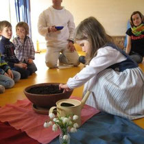 Alle Kinder - im Bild Mira - pflanzen zu Ostern mit Bruder Emmanuel ein Samenkorn
