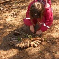 Klara legt ein Bild aus Materialien der Natur.