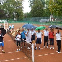 Aktive mit Regenschirm beim Tennisspielen