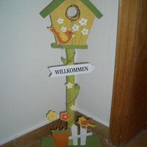 Herzlich Willkommen in Unserem Haus - Willkommen und ein Vogelhaus an einem Holzstab
