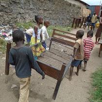 Die Kinder tragen die Betten aus dem alten Gebäude