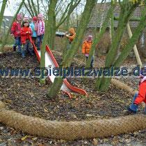 Spielplatzwalzen begrenzen einen Bereich mit Holzschnitzeln
