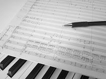 Handgeschriebene Partitur und Bleistift, Klaviatur