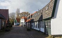"""<img src=""""image.jpg"""" alt=""""Straatje met oude huizen in De Waal op Texel."""">"""