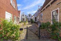 """<img src=""""image.jpg"""" alt=""""'t Hofje met oude huizen in de Weverstraat in Den Burg op Texel."""">"""