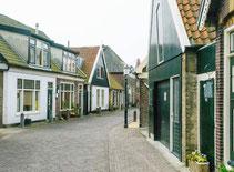 """<img src=""""image.jpg"""" alt=""""Straatje in Oosterend op Texel met pittoreske huizen. """">"""