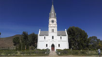 the local church in nieu bethesda, south africa with trees and bushes and a fence and a gate and the sky