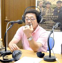 ラジオの生放送で殿堂入りの記念指輪の話をする具志堅さん=20日夕、FMいしがきサンサンラジオ