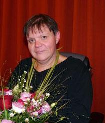 Auf dem Foto sitzt Andrea Lauer vor einem roten Vorhang. Sie hat Blumen von der Preisverleihung in der Hand.