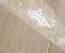 Polished Jerusalem Gold limestone mosaic between beige porcelain field tiles